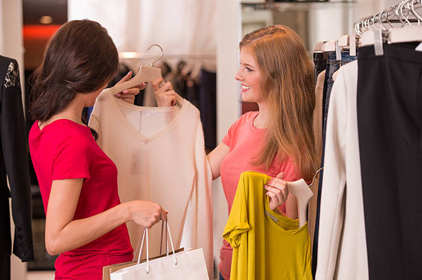 Two Women shopping choosing dresses stock photo