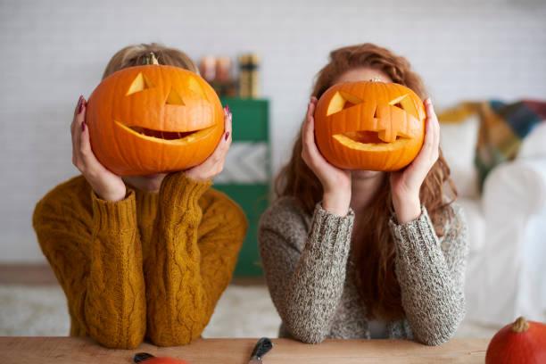 zwei frauen zeigen halloween kürbisse - schnitzmesser stock-fotos und bilder