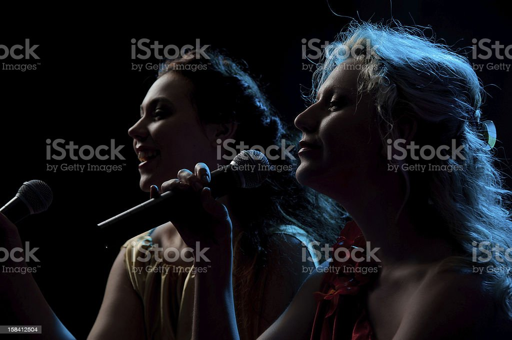 Two women singing in microphone stock photo