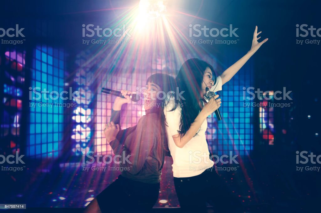 Two women singing in the night club stock photo