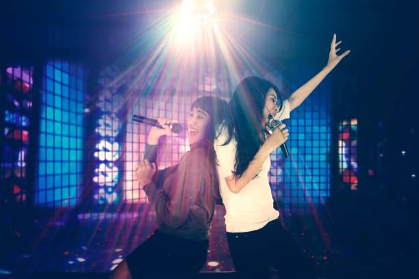 Dos mujeres cantando en el club nocturno - foto de stock