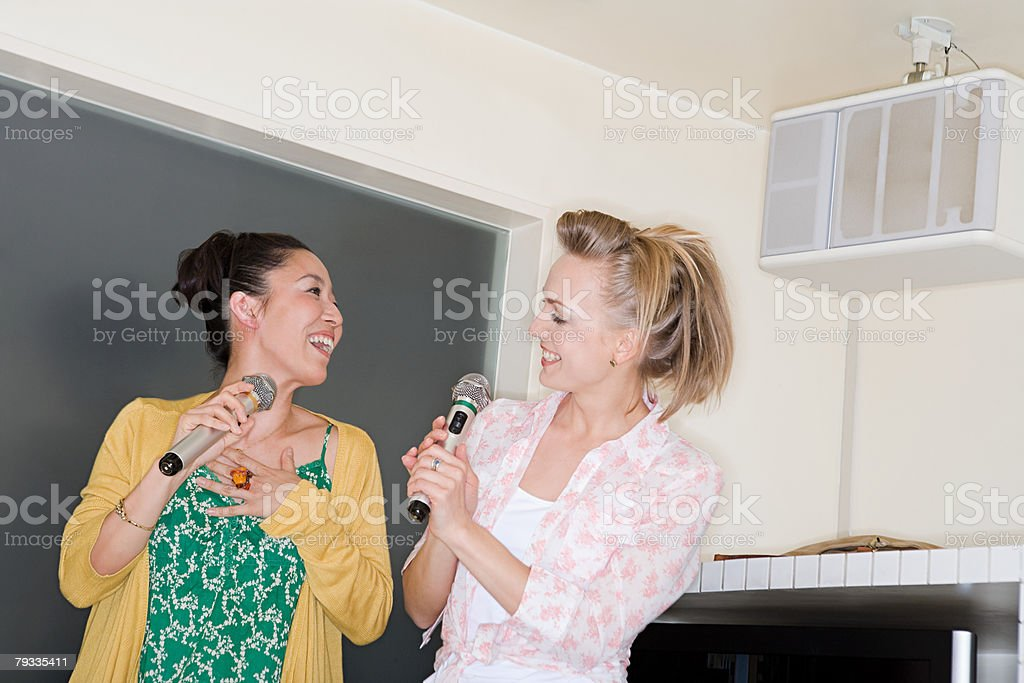 Two women singing karaoke royalty-free stock photo