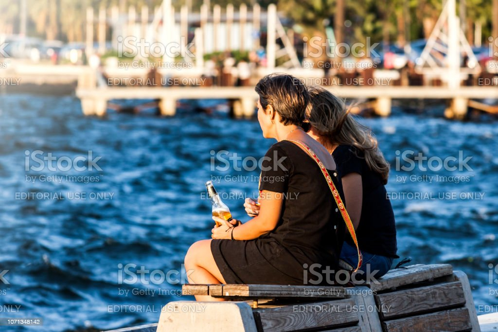 Two Women Sitting And Chatting At Seaside In Izmir Izmir Turkey 18 September 2018 Stock Photo Download Image Now Istock