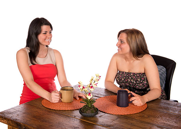 Two women sitting having coffee at table stock photo