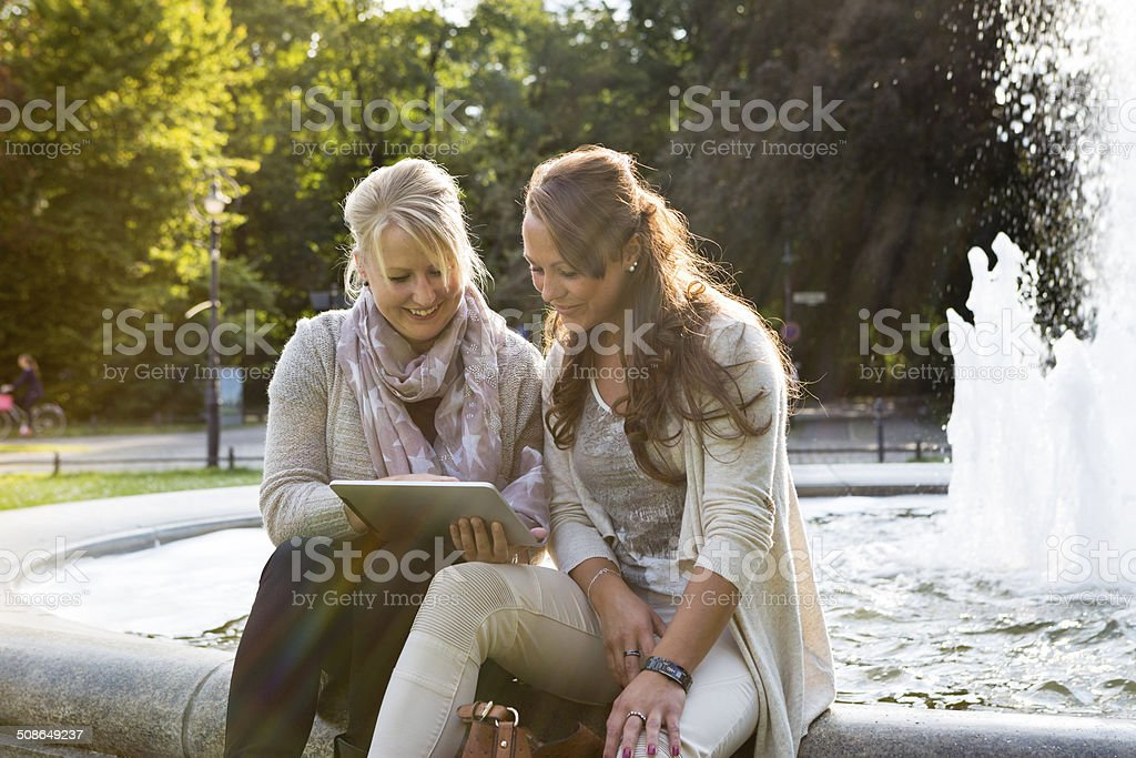 two women sitting in front of fountain using digital tablet stock photo