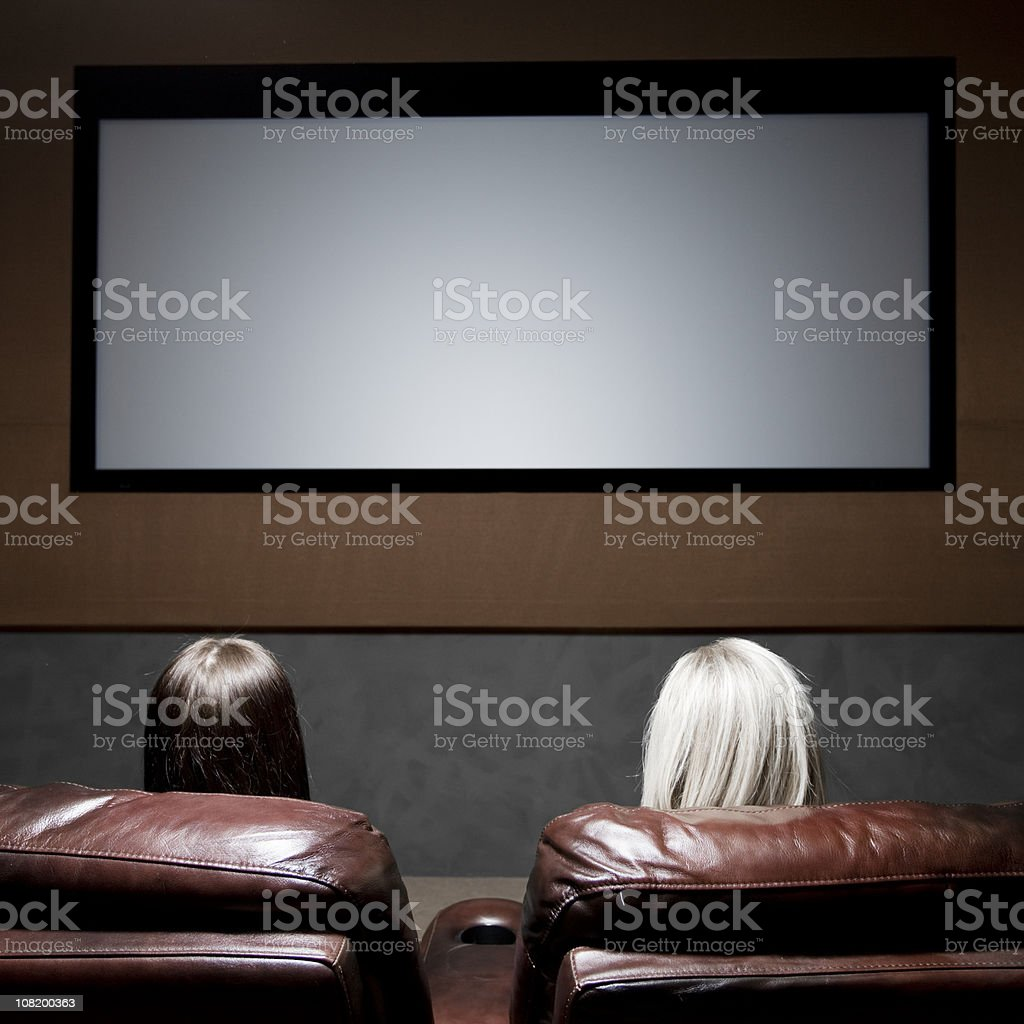 Two Women Sitting in Home Movie Theatre with Blank Screen royalty-free stock photo