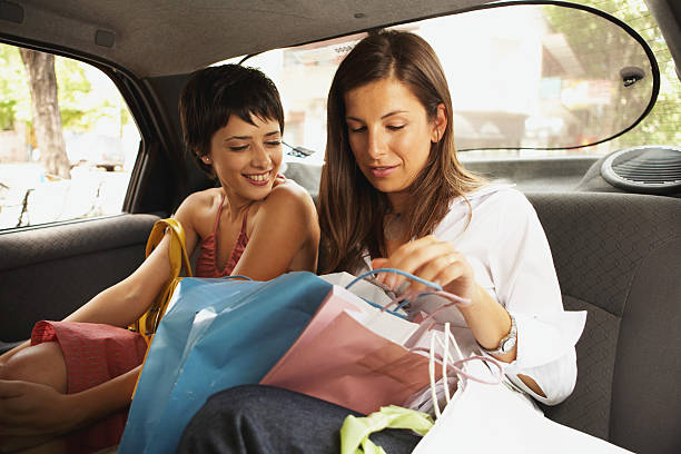 Zwei Frauen sitzen in einem taxi mit shopping Taschen und Lächeln – Foto