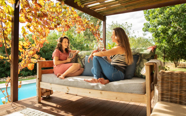 Two women sitting on a patio and talking over glasses of wine stock photo