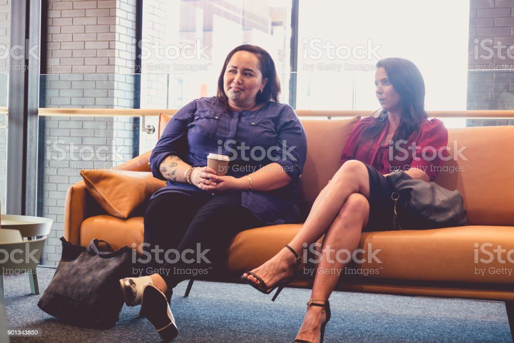 Two women sitting on couch in waiting room, office lounge or business reception area - could be candidates for job interview. Photographed in Auckland, New Zealand, NZ. stock photo
