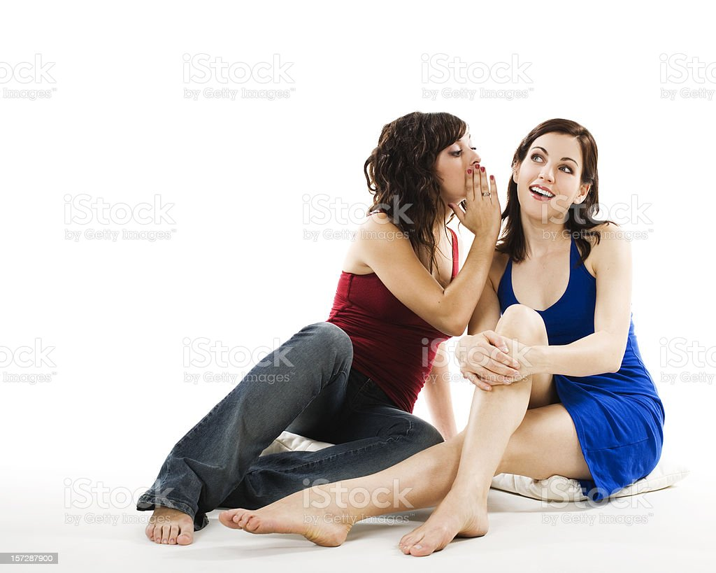 Two women sitting on the ground whispering secrets royalty-free stock photo