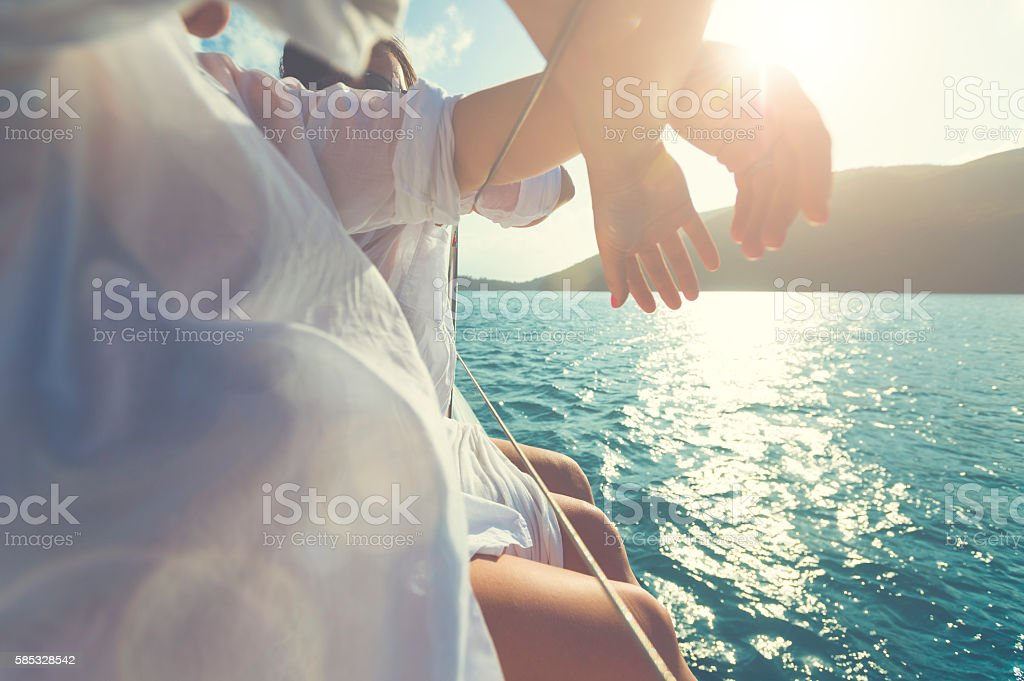 Two women sitting on the side of a sailboat stock photo