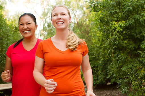 istock Two women smiling and walking outdoors 175542556