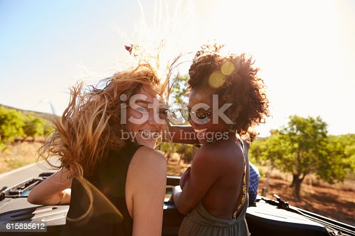 istock Two women standing in the back of open car turning 615885612