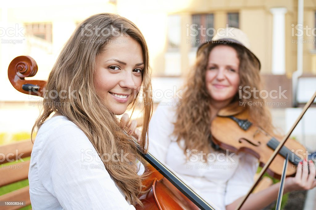 Two women strings duet playing violin and cello on street stock photo