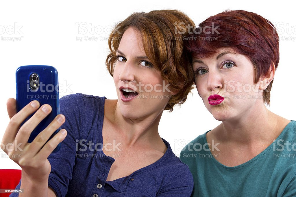 Two women taking self portraits with a cell phone royalty-free stock photo