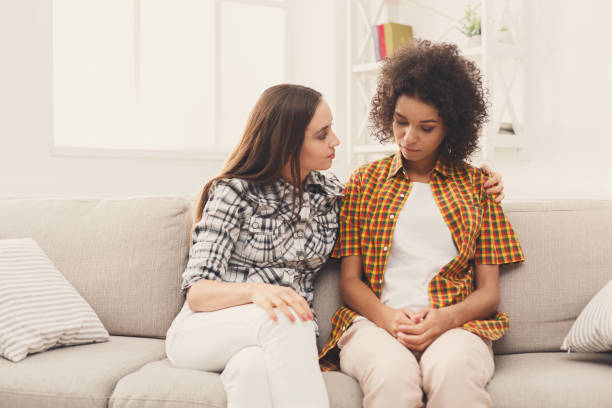 Two women talking about problems at home stock photo