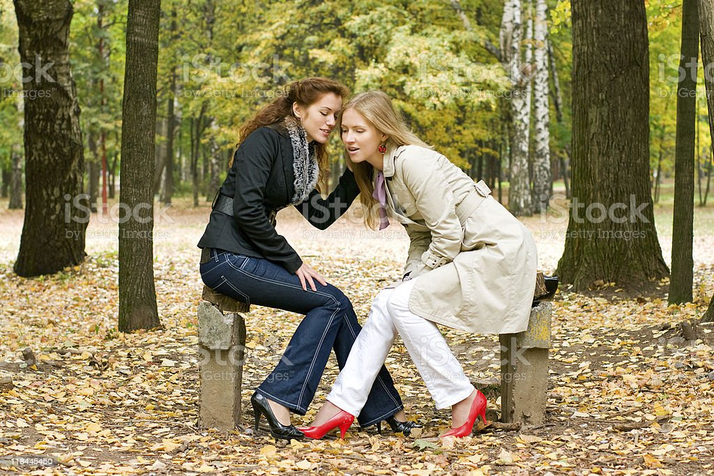 Two women talking in autumn park royalty-free stock photo