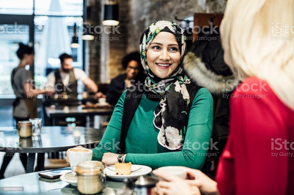 Two women talking in cafe with drinks and food stock photo