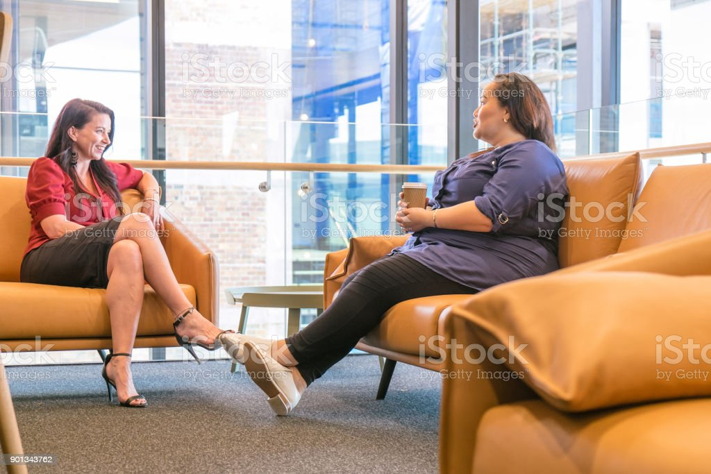 Two women talking in waiting room, reception or business office lounge area in Auckland, New Zealand, NZ stock photo