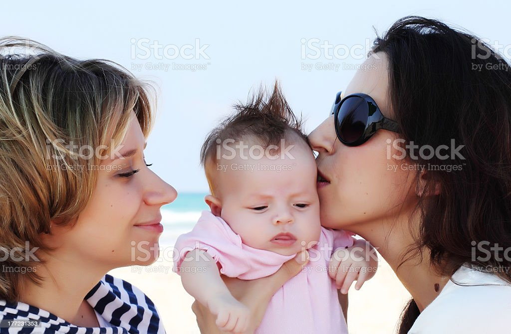 Two women talking to and kissing a very young baby royalty-free stock photo