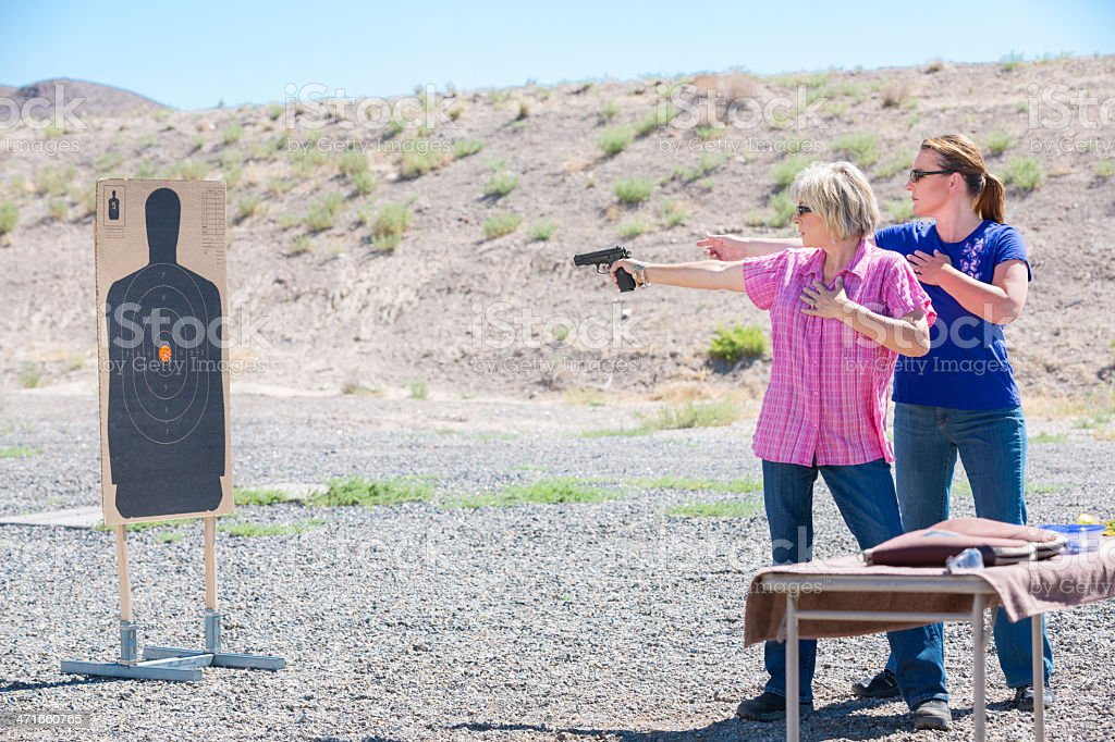 Two women target shooting at the outdoor range royalty-free stock photo