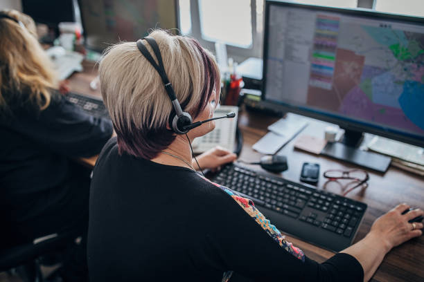 Two women taxi service operator with headsets working in call centre stock photo