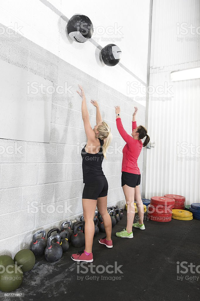 Two women throws medicine balls in fitness gym stock photo