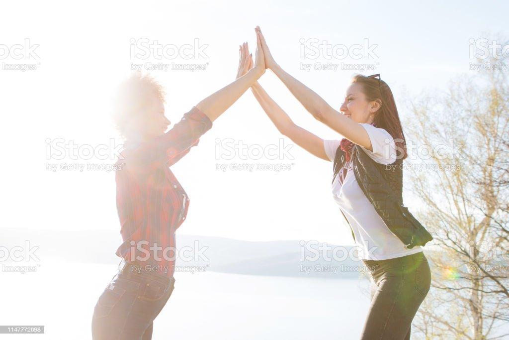 Two women tourist. Hiking people reaching summit top giving high five...