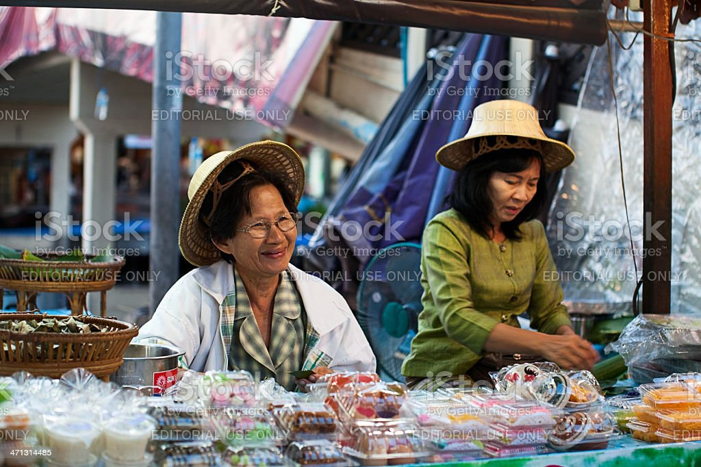 Two women trading food at Floating Market in Thailand royalty-free stock photo