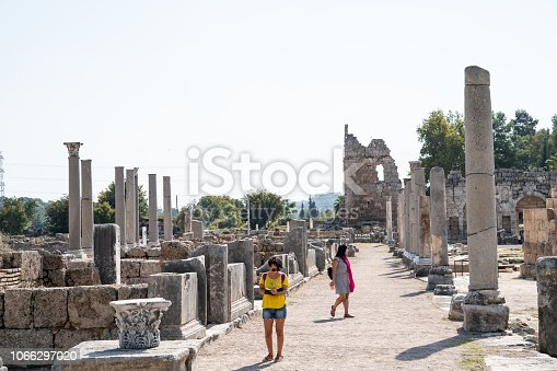 Two women travelers walking in antique Roman city of Perge, Antalya, Turkey. They are in casual clothing. Shot in outdoor daylight with a full frame mirrorless camera.