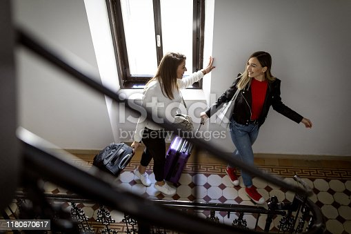 Two women travelling with suitcases and looking for their apartment