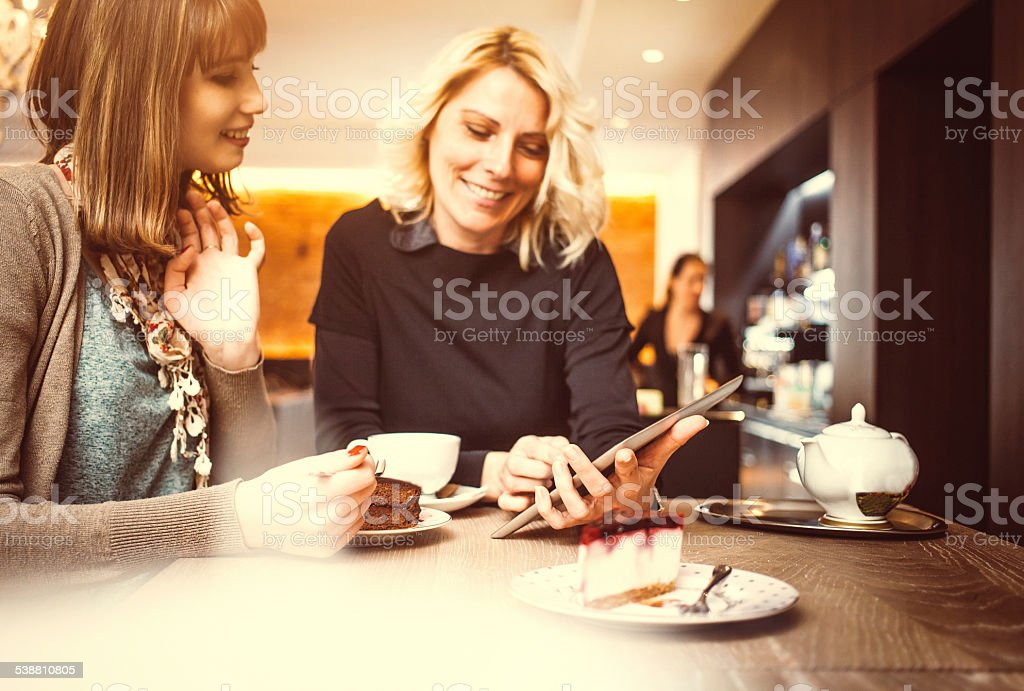 Two women using digital tablet at the coffee shop stock photo
