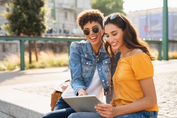 dwie kobiety korzystające z tabletu cyfrowego na zewnątrz - przyjaźń zdjęcia i obrazy z banku zdjęć