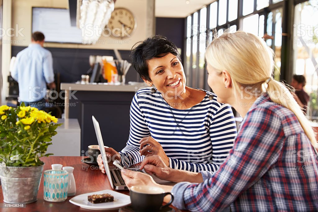 Two women using laptop computer in a coffee shop stock photo