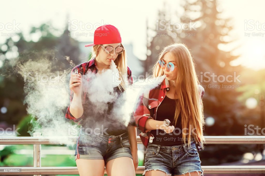 Two women vaping outdoor. The evening sunset over the city. Toned image stock photo