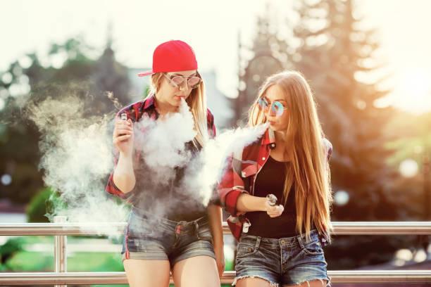 두 여자 vaping 야외입니다. 도시의 저녁 일몰입니다. 몸매 이미지 - 전자담배 뉴스 사진 이미지