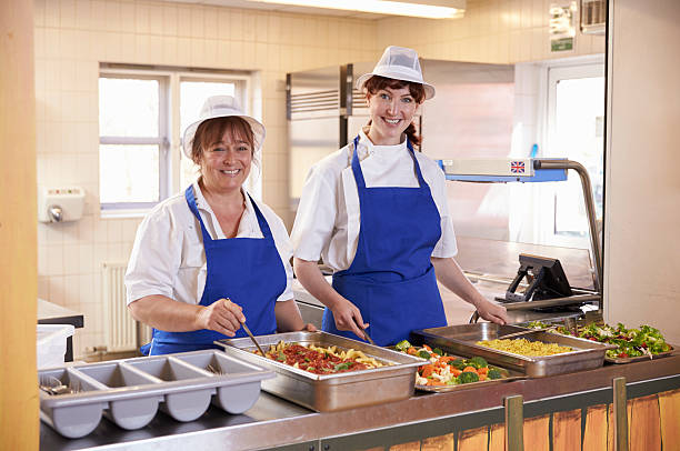 Two women waiting to serve lunch in a school cafeteria stock photo