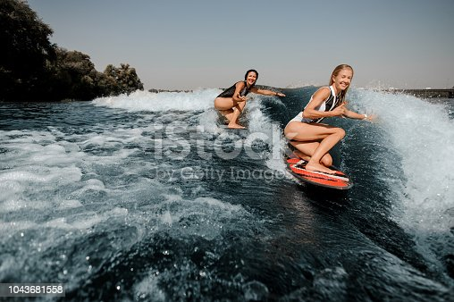 Two sexy happy women wakesurfing on boards down the blue wave on hot sunny day