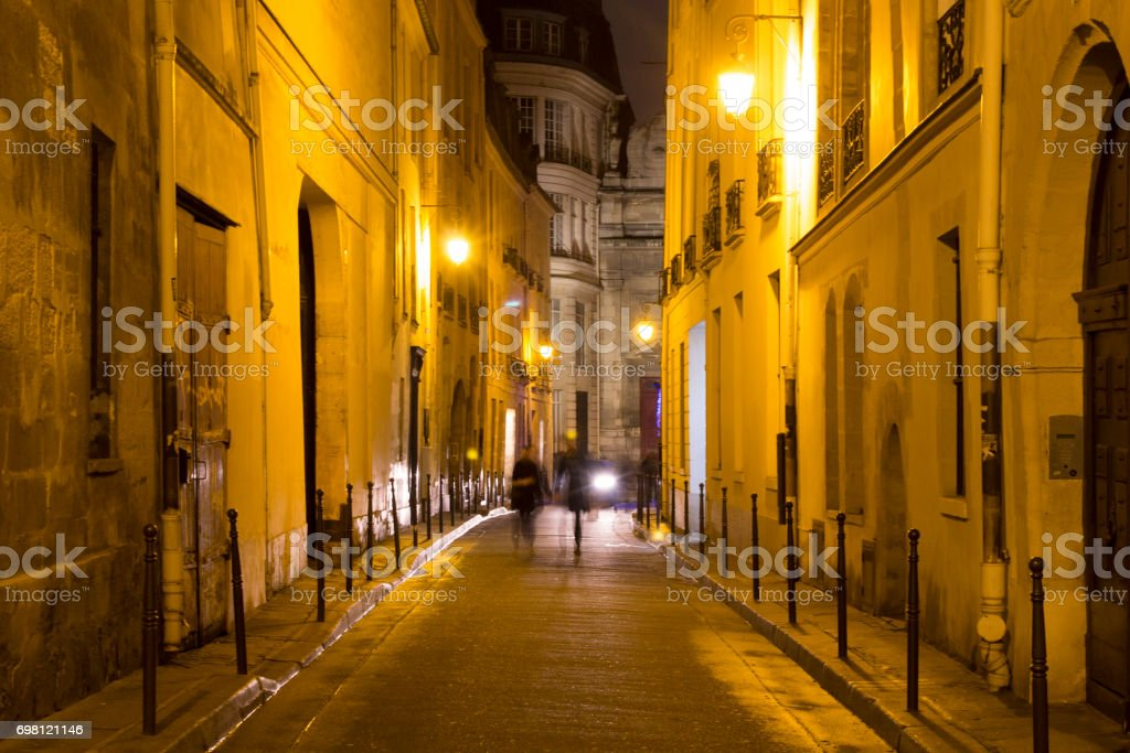 Two women walk in blurry motion at night on one of the streets of Le Marais district in Paris. It's night time. The district hosts many outstanding buildings of historic and architectural importance stock photo