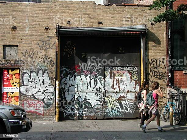 Two women walk past heavily graffiti'd wall. East Village SOHO