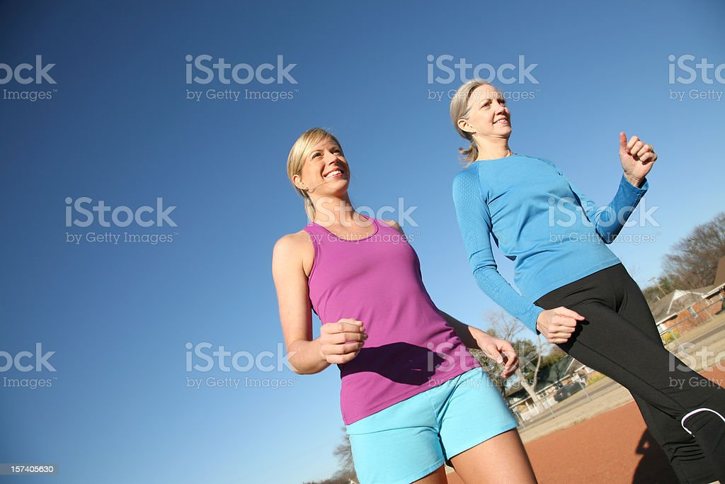 Two Women Walking Around A Track In Spring royalty-free stock photo