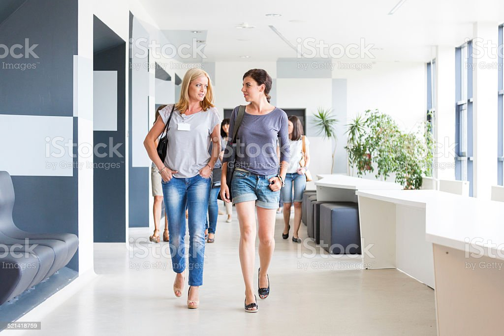 Two women walking down the hall Two young woman walking down the hall in modern interior and talking. Activity Stock Photo