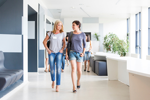 Two Women Walking Down The Hall Stock Photo - Download Image Now