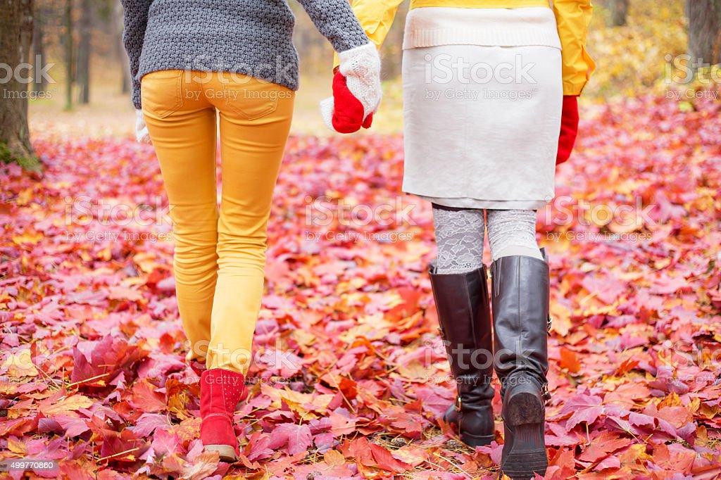 Two women walking in park stock photo