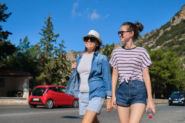 Dağ yolunda güneşli yaz gününde yürüyen iki kadın stok fotoğrafı