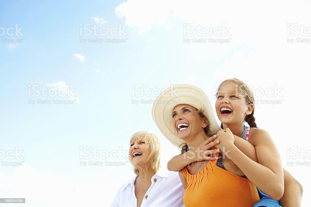 Two women walking with a girl enjoying a piggyback ride stock photo