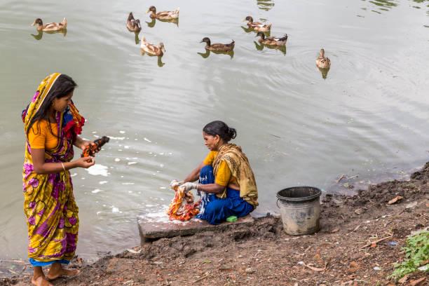 Rajshahi, Bangladesch - 6. Juli 2016: Zwei Frauen waschen bunten Saris in einem See mit Enten – Foto