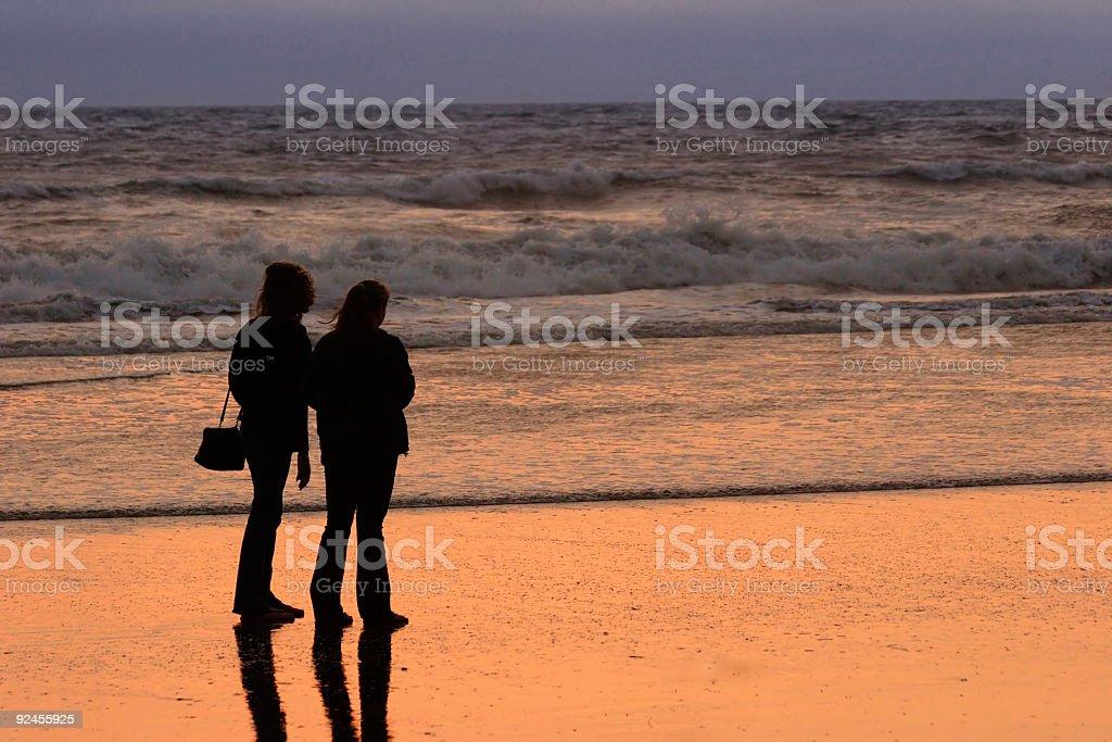 Two women watching the beach sunset royalty-free stock photo