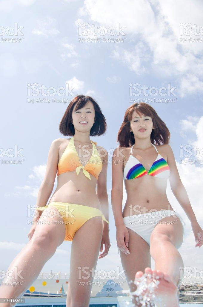 兩名婦女身穿泳裝,踢了踢地上的水 免版稅 stock photo