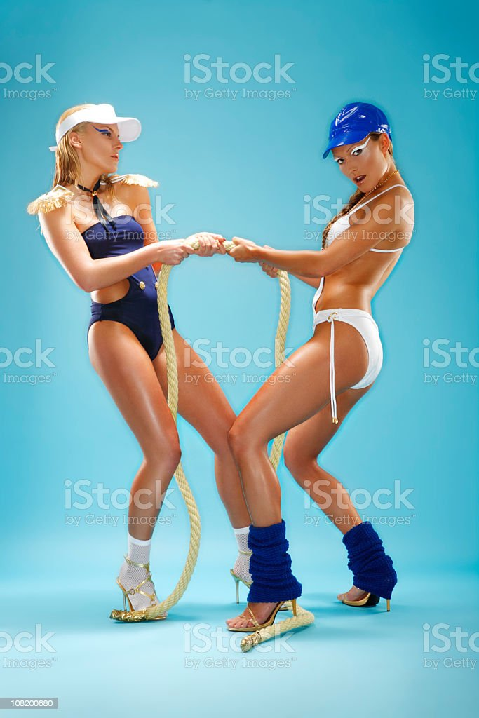 Two Women Wearing Bathing Suits and Tugging on Rope royalty-free stock photo
